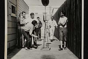 """//en.wikipedia.org/wiki/File:Wallace_Berman_and_friends_in_the_alley_next_to_the_Ferus_Gallery_showing_a_Wally_Hedrick_sculpture_to_the_LAPD_vice_squad_in_1957.jpg 